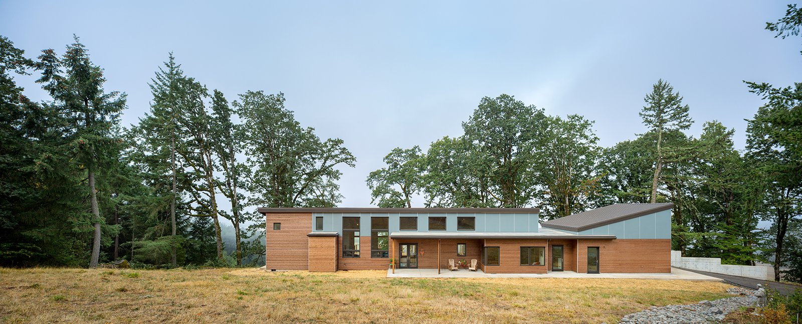 Cedar siding and fiber cement panels, painted a soft blue grey, assures the home blends into the natural landscape. The home's linear plan and shed roofs takes full advantage of the site's views and solar orientation.