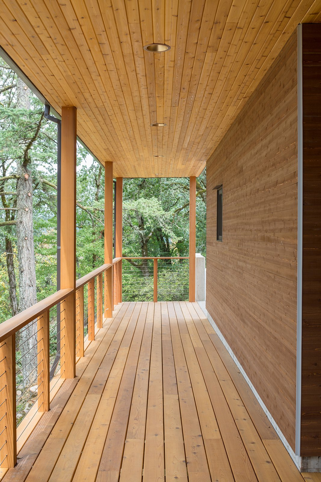 The covered walkway is enveloped by cedar planks and lush oak canopies.
