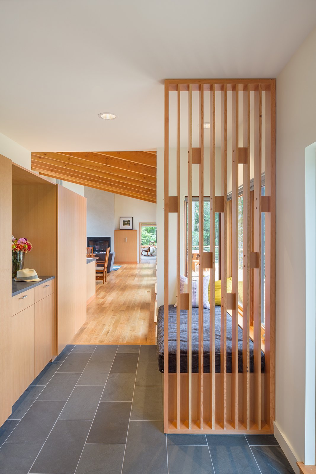 A playful wood screen greets visitors at the front entry, as well as providing support for a cushioned bench seat. Durable materials such as the Doug Fir cabinetry, White Oak flooring and a slate tile floor provide warmth and longevity.