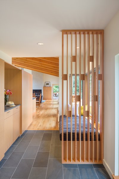 A playful wood screen greets visitors at the front entry, as well as providing support for a cushioned bench seat. Durable materials such as the Doug Fir cabinetry, White Oak flooring and a slate tile floor provide warmth and longevity. Photo 4 of Sunset Knoll House modern home