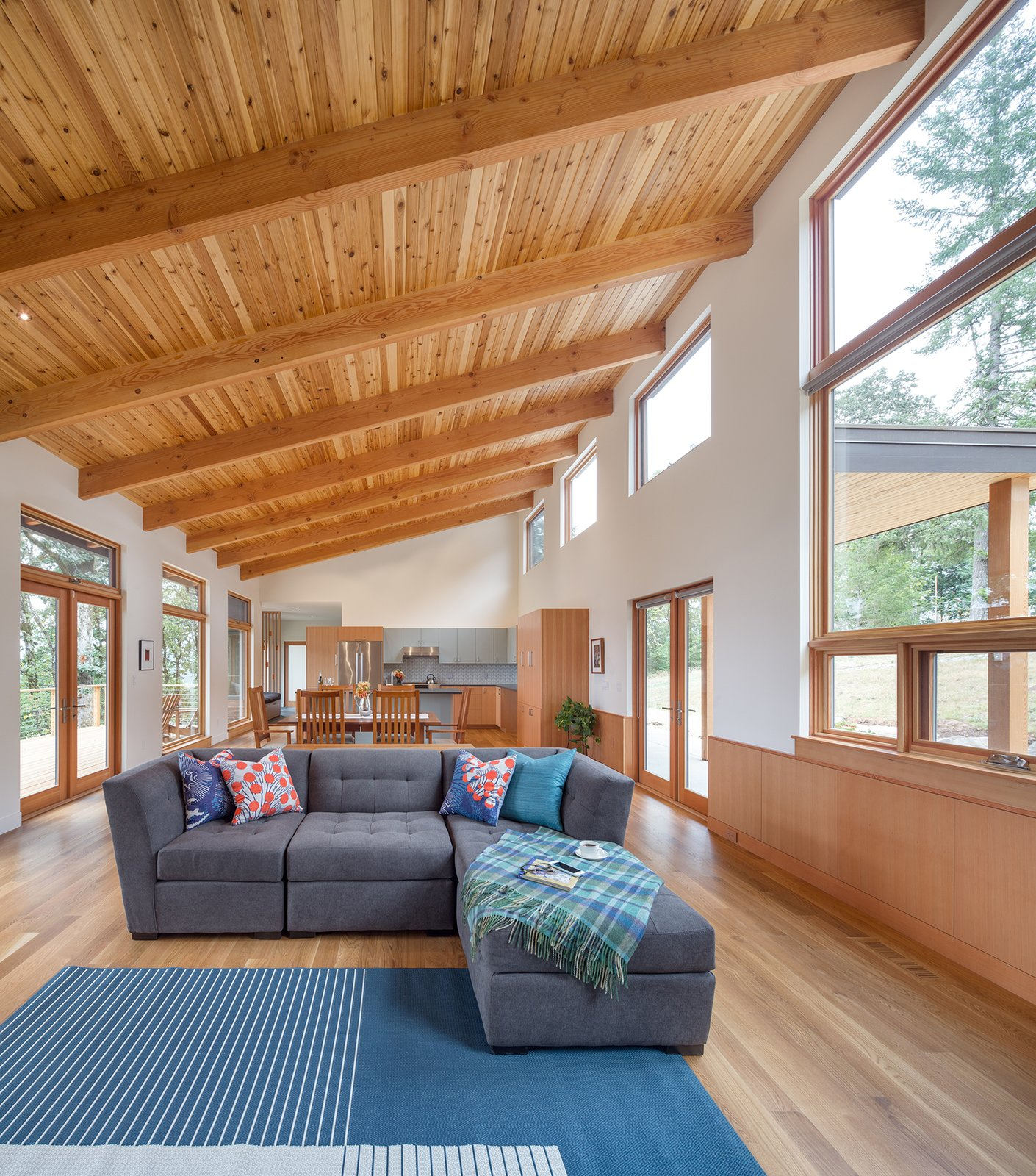 The great room, housed under a dramatic tongue and groove Cedar soffit, is flanked by views towards the East and West.