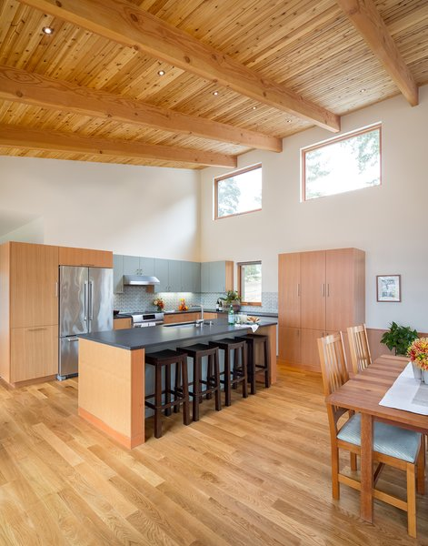 The kitchen defines the Northern edge of the great room.  High East facing windows bathe the room in early morning light.   Photo 7 of Sunset Knoll House modern home