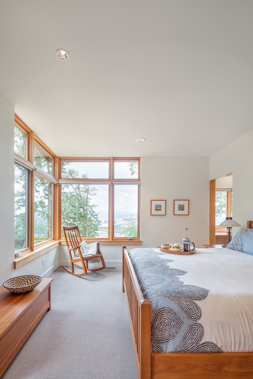 Full height corner windows in the master bedroom frame views towards the Yamhill Valley beyond.