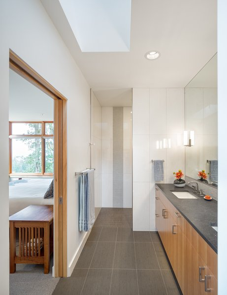 A sculptural skylight bathes the master bathroom in natural light.  A single level of tile floor allows easy access to the full height glass shower at the room's end. Photo 9 of Sunset Knoll House modern home