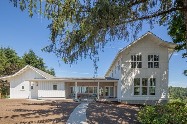 The home's wide entry porch welcomes visitors and family alike. The crisply painted board and batten wood siding reflects the region's vernacular agrarian roots.  Photo  of Shadowood House modern home