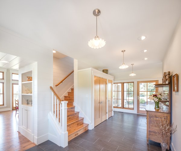 Vintage light fixtures add warmth and rustic charm to the base of the main stairwell. Built in cabinets and niches blend with the owner's antique furnishings. Photo 4 of Shadowood House modern home
