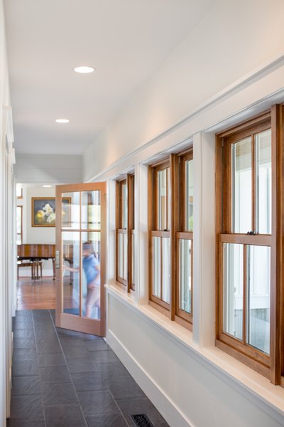 A row of single hung wood windows defines the entry hallway with views towards the front porch. Photo 5 of Shadowood House modern home
