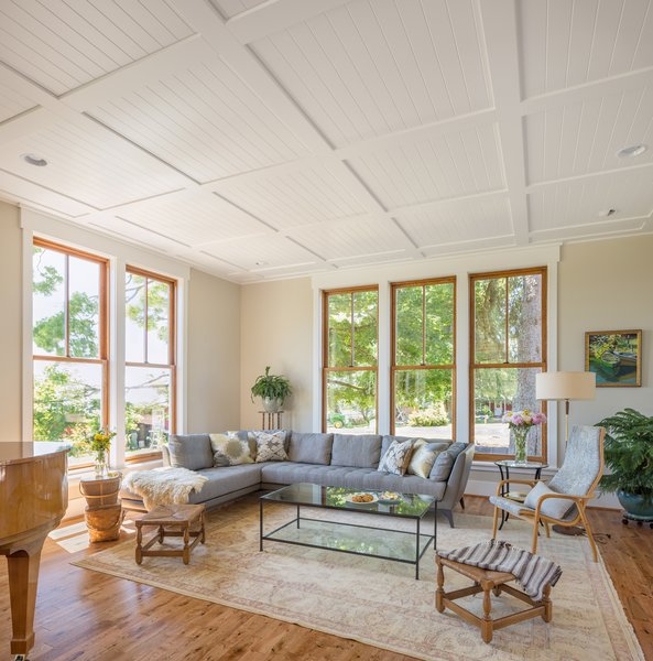 The home's living room is bathed in natural sunlight with views towards the rolling pastures beyond. The ceiling is defined with crisp white tongue and groove panels.  Photo 6 of Shadowood House modern home
