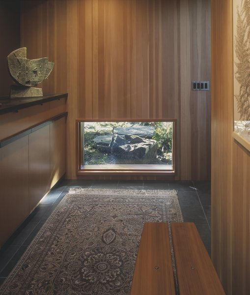 A low window frames the view of the garden's quiet fountain, set within a series of basalt boulders.  Wood paneled walls and slate floors are in keeping with the home's original 1949 materials. Photo 5 of Belluschi Addition modern home