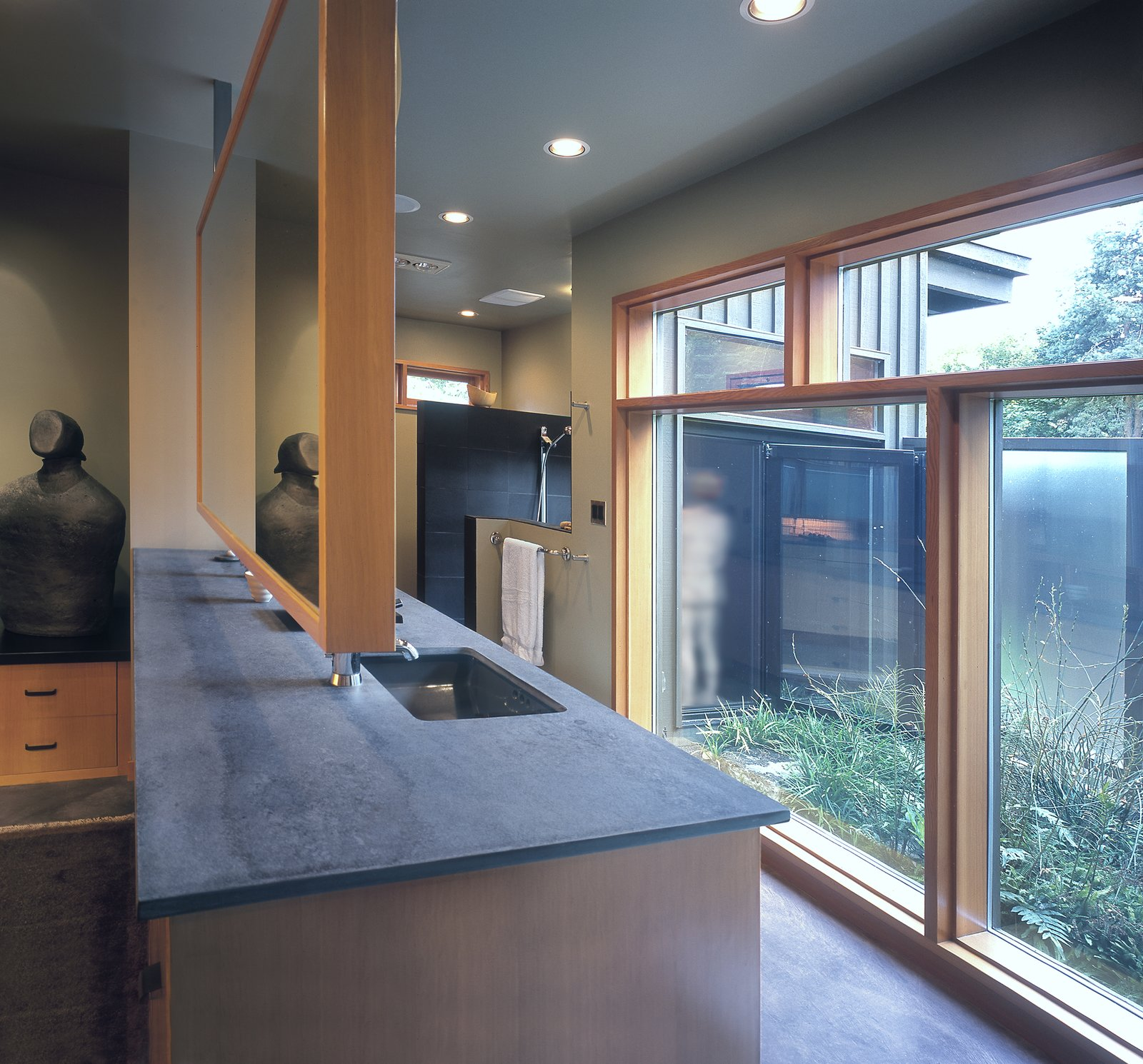 The Master Bathroom addition opens to a private garden court. The room features timeless materials such as Fireslate countertops and Douglas Fir casework.  Belluschi Addition by Richard Brown Architect