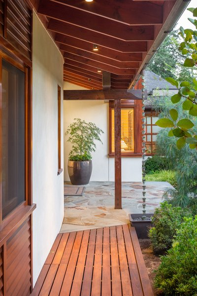 The entry displays a diversity of wood species: Mahogany panels at the wall, a Cedar slat walkway and Douglas Fir framing members.  A copper rain chain diverts rain water to the entry planting bed. Photo 3 of Lakeside House modern home