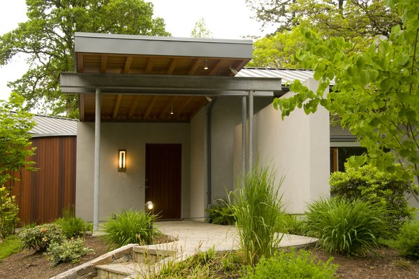 A Mahogany wood soffit cantilevers over the home's entry. Photo  of Cedar Mills House modern home
