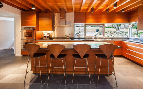 The kitchen features Mahogany cabinetry, dark granite counters  and counter height windows with views towards the backyard. Photo 7 of Cedar Mills House modern home