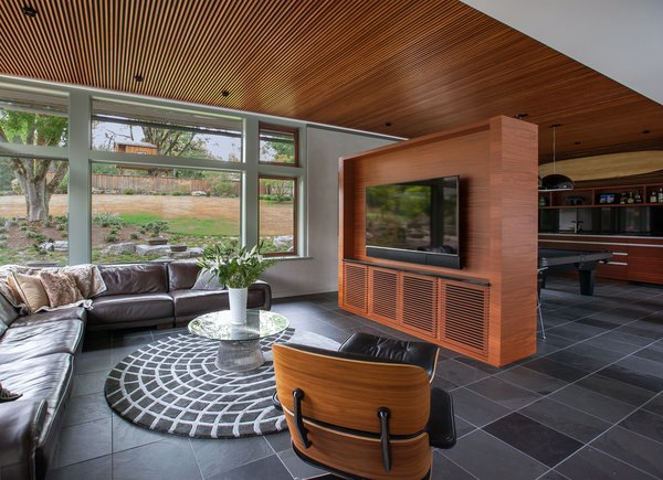 The family room features Mahogany cabinetry housing all the family's electronics, separating the tv viewing area from the billiards table. Photo 10 of Cedar Mills House modern home