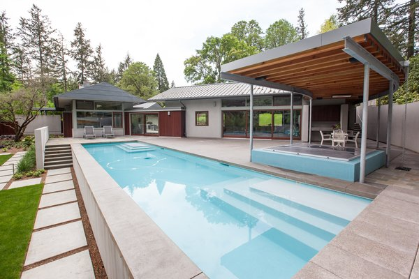 The pool is surrounded by a generous terrace and features a covered hot tub and seasonal kitchen.  Photo 12 of Cedar Mills House modern home