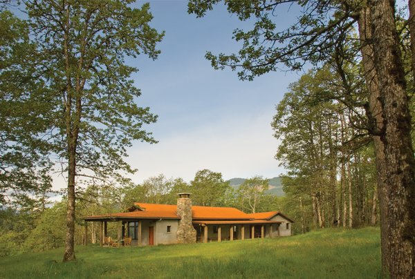In autumn, the mineral rust color of the standing seam metal roof blends the home into the canopy of surrounding oaks. Photo  of Columbia Gorge House modern home