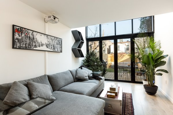 Back wall replaced with floor to above ceiling level glass windows and doors Photo  of Brooklyn Railroad Townhouse to Open Plan Renovation modern home