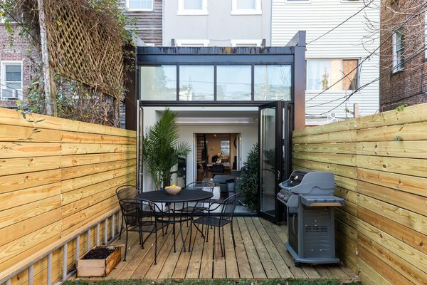 Rear deck with open atrium seamlessly extends the indoor space into the outdoor space Photo 4 of Brooklyn Railroad Townhouse to Open Plan Renovation modern home