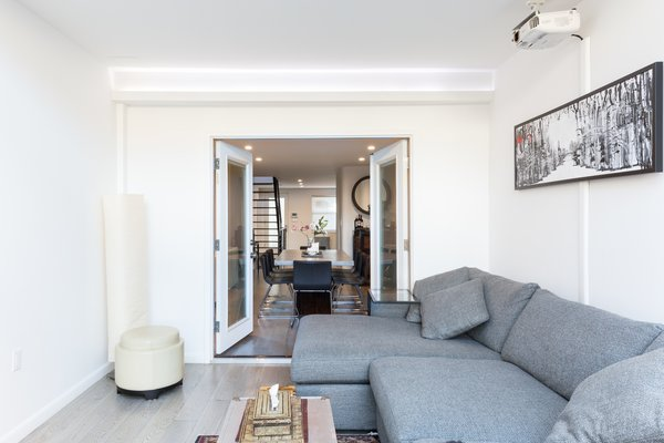 French doors create an open flow from the dining room to the living room and atrium  Photo 6 of Brooklyn Railroad Townhouse to Open Plan Renovation modern home
