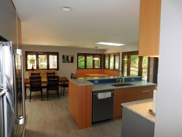 Modern home with kitchen, wood cabinet, ceramic tile floor, colorful cabinet, recessed lighting, refrigerator, range, glass tile backsplashe, range hood, beverage center, drop in sink, and dishwasher. Photo 3 of The Mason Project