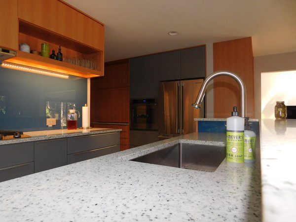 Modern home with kitchen, ceramic tile floor, wood cabinet, stone counter, colorful cabinet, wall oven, refrigerator, range hood, glass tile backsplashe, recessed lighting, range, dishwasher, beverage center, and drop in sink. Photo 4 of The Mason Project