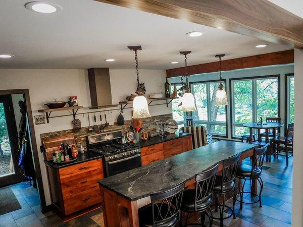 Modern home with kitchen, stone tile backsplashe, wood cabinet, slate floor, stone counter, recessed lighting, pendant lighting, range, and range hood. Photo 6 of The Ranheim Project