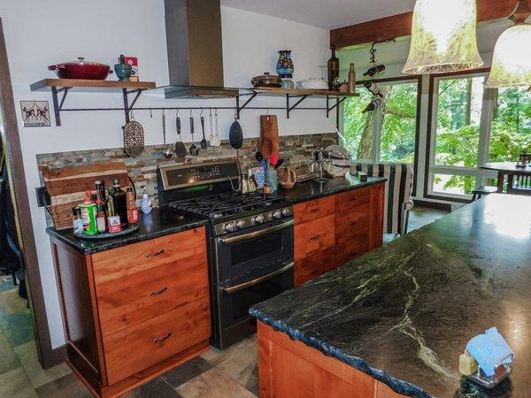 Modern home with kitchen, stone counter, slate floor, wood cabinet, pendant lighting, recessed lighting, stone tile backsplashe, range, and range hood. Photo 7 of The Ranheim Project