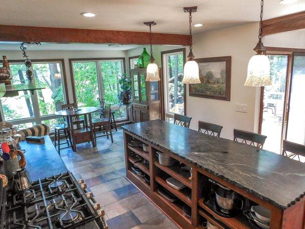 Modern home with kitchen, wood cabinet, stone tile backsplashe, stone counter, recessed lighting, pendant lighting, slate floor, range, and range hood. Photo 8 of The Ranheim Project