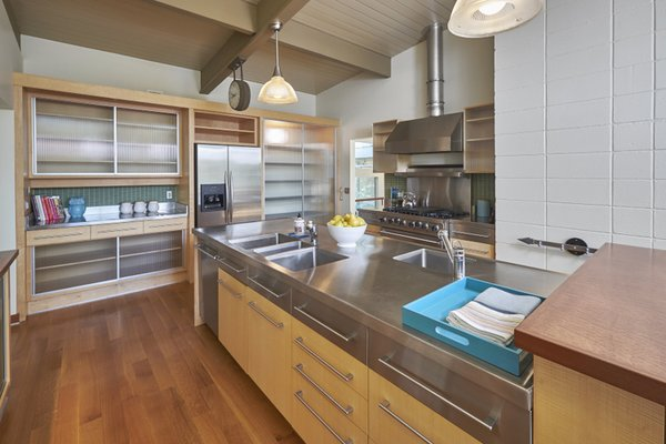 Modern home with kitchen, metal counter, wood cabinet, metal cabinet, medium hardwood floor, ceramic tile backsplashe, pendant lighting, accent lighting, refrigerator, dishwasher, range hood, range, and undermount sink. Photo 3 of The Alexander Project