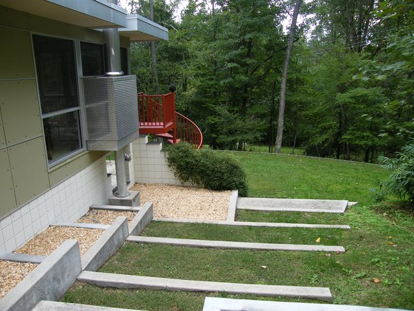 Modern home with shrubs, walkways, raised planters, gardens, hardscapes, concrete patio, porch, deck, planters patio, porch, deck, landscape lighting, staircase, metal tread, and metal railing. Photo 10 of The Alexander Project