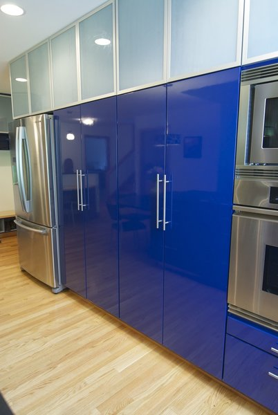 Modern home with colorful cabinet, wood cabinet, light hardwood floor, recessed lighting, wall oven, refrigerator, storage room, and cabinet storage type. Photo 7 of The Domino-Scotti Kitchen