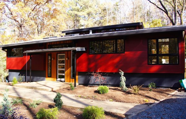 Modern home with walkways, front yard, flowers, shrubs, trees, small patio, porch, deck, wood patio, porch, deck, decking patio, porch, deck, picture window type, wood, swing door type, exterior, and windows. Front Photo  of The Ross-Yarger Project