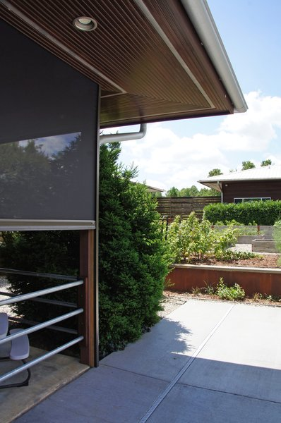 Modern home with outdoor, wood fence, metal fence, large patio, porch, deck, horizontal fence, concrete patio, porch, deck, metal patio, porch, deck, wood patio, porch, deck, flowers, raised planters, grass, shrubs, walkways, gardens, hardscapes, and back yard. Photo 7 of The Holt-Bottomly Project