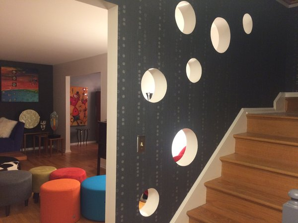 The bubble circles in the wall between living room and stair case bring in natural sun light to the stair case. Photo 9 of The Bubbles House modern home