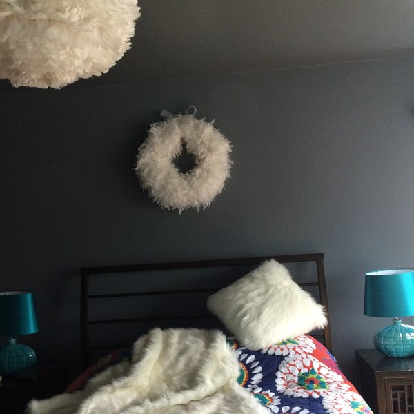 The home owners like to have a calm and quiet bedroom.  The dark gray wall color provides exact that.  White feather pendent and feather shawl with pillows contrast the dark gray wall and add comfort and coziness to the room. Photo 16 of The Bubbles House modern home