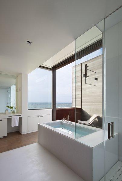 Modern home with bath room, engineered quartz counter, enclosed shower, medium hardwood floor, soaking tub, and recessed lighting. Photo 3 of Sagaponack, NY