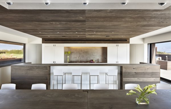 Modern home with dining room, bar, table, chair, stools, ceiling lighting, and ceramic tile floor. Photo 4 of Sagaponack, NY