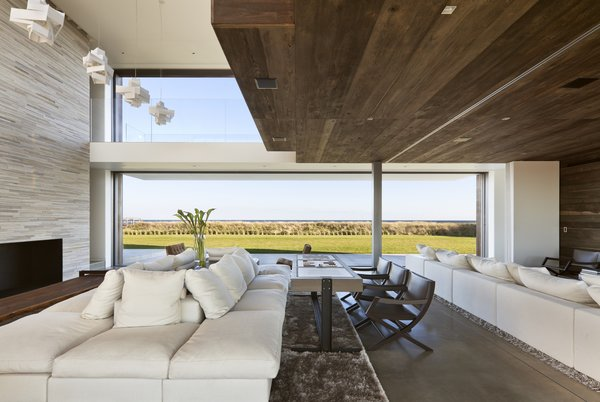 Modern home with living room, sectional, sofa, ribbon fireplace, ceiling lighting, pendant lighting, accent lighting, and recessed lighting. Photo 7 of Sagaponack, NY