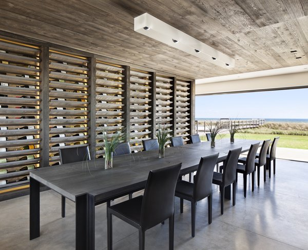 Modern home with dining room, chair, table, shelves, and ceiling lighting. Photo  of Sagaponack, NY