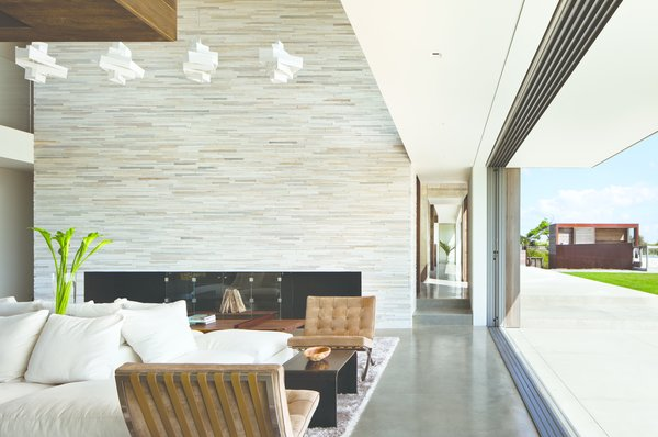 Modern home with living room, ribbon fireplace, accent lighting, ceiling lighting, pendant lighting, sectional, chair, sofa, and console tables. Photo 2 of Sagaponack, NY