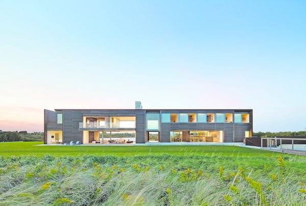 Modern home with outdoor, back yard, large patio, porch, deck, large pool, and grass. Photo 5 of Sagaponack, NY