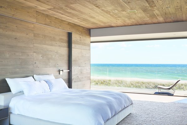 Modern home with bedroom, bed, chair, night stands, recessed lighting, and ceiling lighting. Photo 9 of Sagaponack, NY
