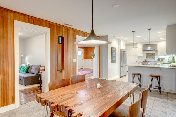 Dining area has reclaimed timber dining table handcrafted in Portland and a Gubi semi pendant from Design Within Reach. Photo 8 of Chic Mid-Century in Oregon Wine Country modern home