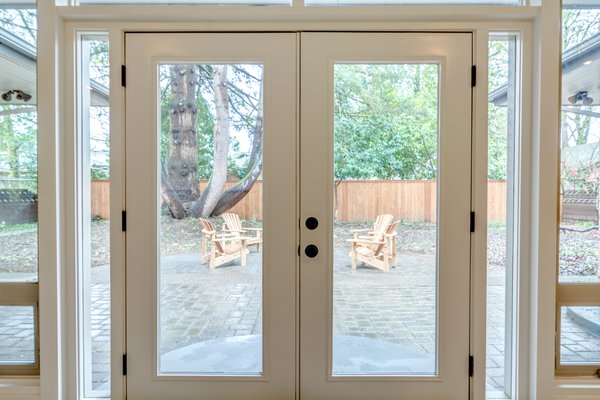 French doors in the living room lead to a beautiful backyard. Photo 15 of Chic Mid-Century in Oregon Wine Country modern home