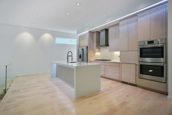 An island takes centre stage within the kitchen and makes use of the golden triangle rule. Photo 4 of 908 Kings Court modern home