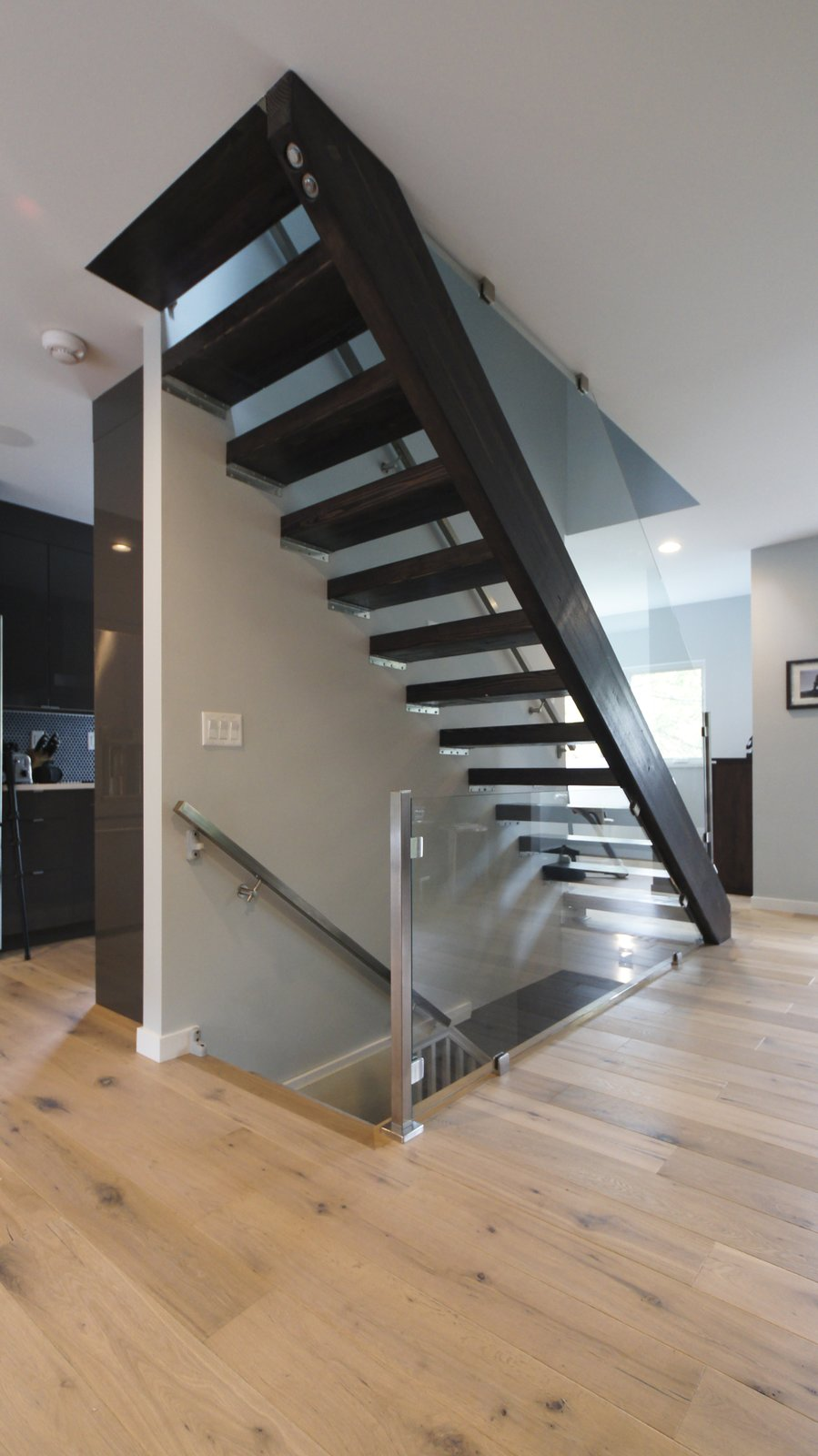 Open risers and glass railings maintain an open flow of space.