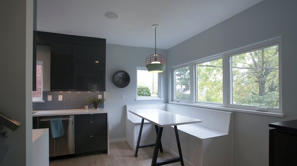 The kitchen is also connected to the front yard, with windows off of the built-in breakfast nook. The breakfast nook offers a casual place to eat, work, or play - while still engaged with what is happening in the kitchen. Photo 7 of Eave House modern home
