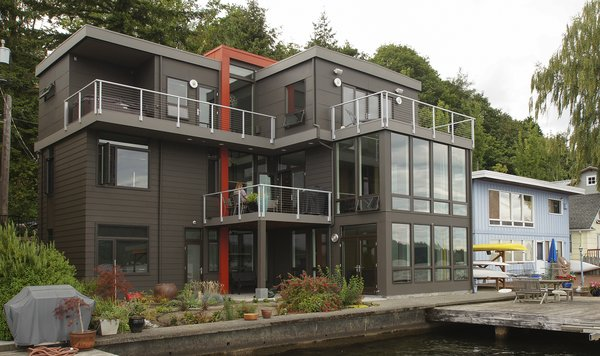 This modern home uses color and siding patterns to help distinguish the house. The large amounts of glazing provide views of the lake from all rooms. Photo 2 of Lake Washington Home modern home