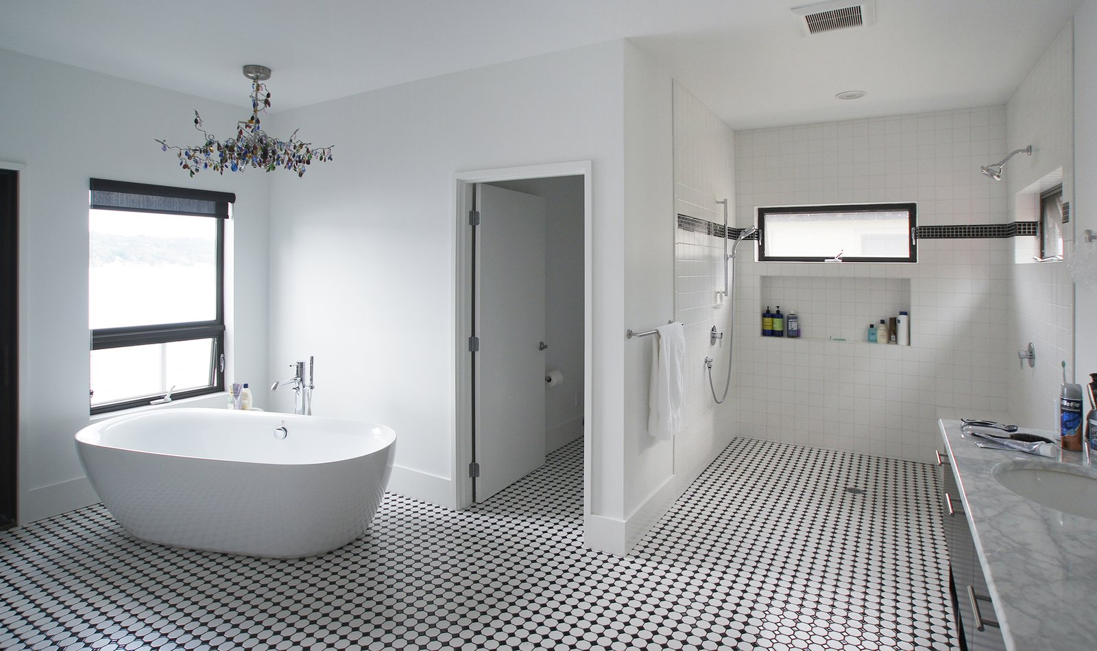 This black and white bathroom is open to the master suite as well as the deck and view beyond.