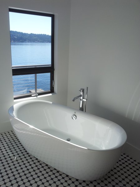 This freestanding tub allows the homeowners to site and enjoy the view during a soak. Photo 5 of Lake Washington Home modern home